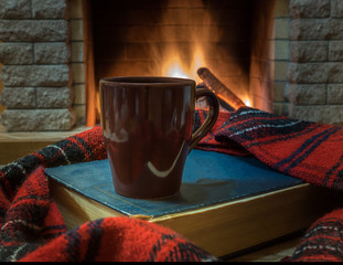 Cozy scene before fireplace with brown mug with tea, a book, and wool scarf.