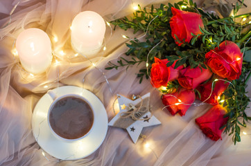 Composition: red roses with boxwood, garlands, candles, star and cup coffee (tea)