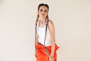 beautiful fashionable woman with braids dancing work overalls