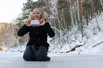 girl on a frozen river takes pictures on the phone