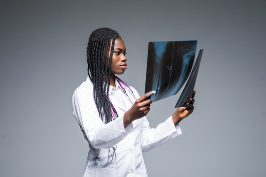Young african Female doctor looking at an x-ray isolated on gray background