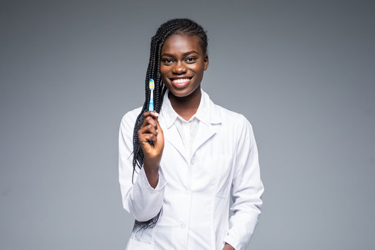Beautiful african female dentist doctor holding and showing a toothbrush isolated on a gray background