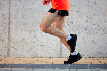 Picture of man's legs running on the street. Healthy lifestyle concept.