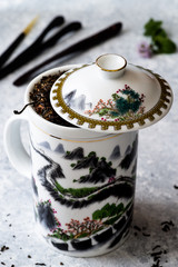 White teapot with 'great wall' design, tea herb, delicate background