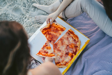 Young couple in love eat pizza on the deserted beach on a summer evening