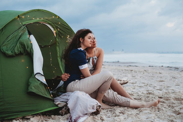 Young loving couple while camping on the seashore a summer evening at sunset. Two women hugging each other