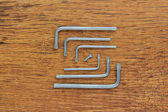 Hex key or allen wrench set on wooden background
