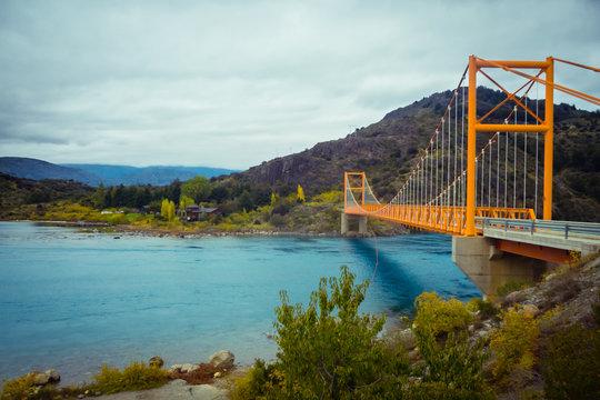 Red suspension bridge over the water runoff of General Carrera Lake, near Lake Bertrand, Puerto Tranquilo, Chile Chico, Aysen, Chile, Patagonia