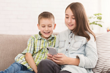 Siblings watching funny videos on smartphone together