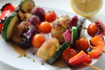 Grilled colorful vegetables skewers on white background.