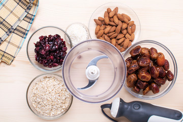 Ingredients for energy bites: nuts, dates, coconut flakes, oatmeal with a food processor on a wooden background.
