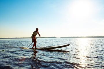 Joyful  guy paddling on a SUP board