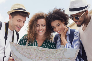 Happy travelers searching the location on city map - fototapety na wymiar
