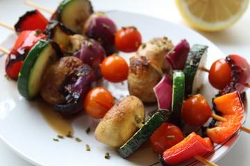 Vegetable skewers on white plate.