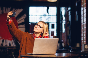 Hipster female blogger making photo on front camera of modern smartphone device sitting in loft cafe or pub interior in evening.Young blond woman taking selfie on mobile phone for social networks.