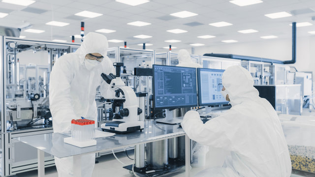 Team of Research Scientists in Sterile Suits Working with Computers, Looking Under Microscope and Modern Industrial Machinery in the Laboratory. Product Manufacturing Process: Semiconductors.