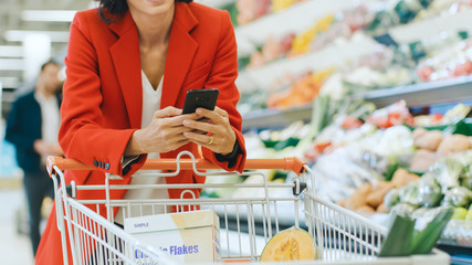 At the Supermarket: Woman Uses Smartphone, Leans on the Shopping Cart. In the Big Mall Woman Browsing In Internet on Her Mobile Phone. Focus on Hands Holding Mobile Phone.