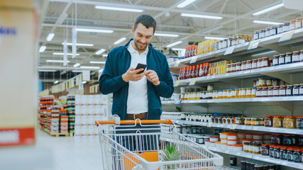 At the Supermarket: Handsome Man Uses Smartphone, Smiles and Stands with Shopping Cart in Canned Goods Section.
