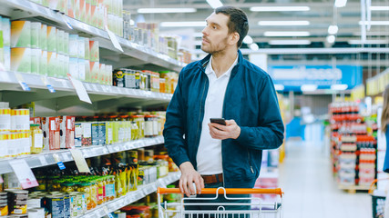 At the Supermarket: Handsome Man Browses Through Shelf with Canned Goods, Places Tin Can into His Shopping Cart and Proceed with His Shopping List Walking Through Different Sections.