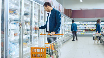At the Supermarket: Handsome Man Pushes Shopping Card and Browses for Products in the Frozen Goods Section. Man Looks into Glass Door Fridge, Looking for Dairy Products.
