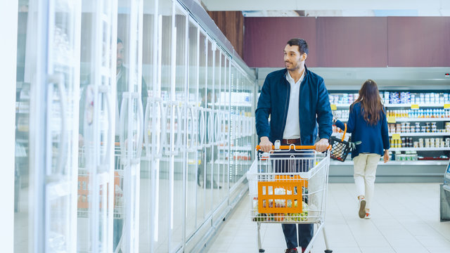 At the Supermarket: Handsome Man Pushes Shopping Card and Browses for Products in the Frozen Goods Section. Man Looks into Glass Door Fridge, Looking for Dairy Products. Customer Shopping
