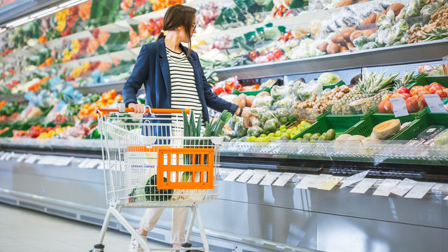 At the Supermarket: Beautiful Young Woman Places Groceries Into Her Shopping Cart. Girl Shopping for Vegetables in the Fresh Produce Section of the Store.