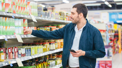 At the Supermarket: Handsome Man Uses Smartphone and Takes Tin Can. He's Standing with Shopping Cart in Canned Goods Section.