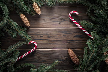 Frame of fur tree and cones. Candy canes on woodden rustic table. Space for text.