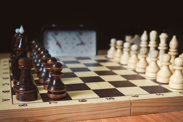 Chess background with a wooden board, chess pieces and clock close-up for all ages