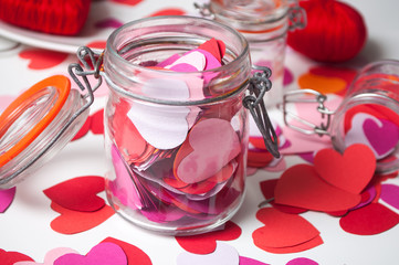 closeup of paper heart falling  from glass container on white background - valentine's day concept