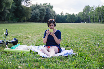 Young adult woman using a smart phone at the public park