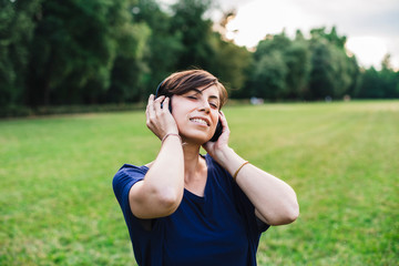 Young adult woman listening music at park