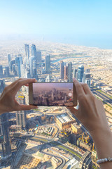 Closeup of woman tourist hand taking photo of Dubai city with smartphone camera from Burj Khalifa tower. Girl taking picture with mobile phone on holiday to post on social media