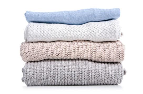 Stack folded sweaters on white background isolation