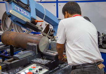 Worker operate band saw machine cutting metal work piece with coolant