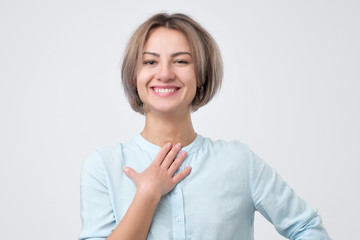 Pleased caucasian woman wearing blue shirt smiling broadly glad to receive compliments from friends