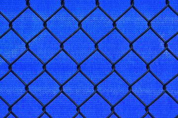Abstract blue mesh tarp behind a black chin link border fence