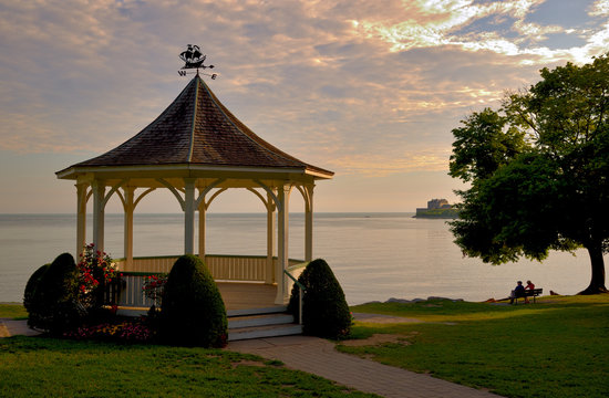 The gazebo at Queens Royal Park, Niagara on the Lake, photographed at sunrise in the summer looking out over Lake Ontario and Fort Niagara with a couple drinking coffee on a bench under a tree