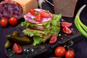 Multi layered club sandwich with rye bread, lettuce salad, sausage, cheese, salted cucumbers and tomatoes on a dark board