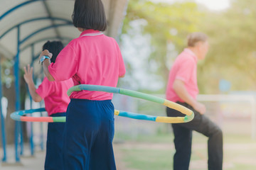 Female students doing exercise with a hula-hoop for a good healt