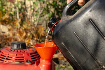 Pouring gasoline into the tank of  lawn mower.