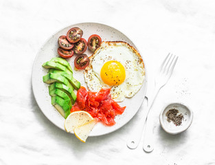 Delicious brunch - fried egg, avocado, cherry tomatoes and smoked salmon on light background, top view