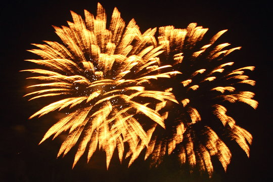 Amber yellow fireworks in the night sky
