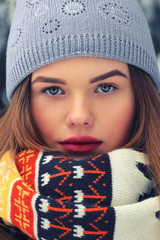 Close up portrait of young woman with blue eyes wearing knitted beanie hat, scarf feeling cold on wintertime. Winter holiday concept. Warm filter