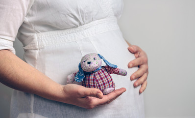Belly of pregnant woman holding a baby rag doll
