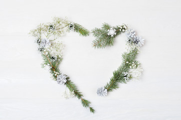 Mockup of Christmas Wreath in form of heart Decorated with white snowflakes and cones. On white wooden background, Flat lay with place for your text. Top view