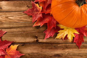 Pumpkin with red maple leafs disposed on wooden table. Flat lay, top view fall autumn concept.
