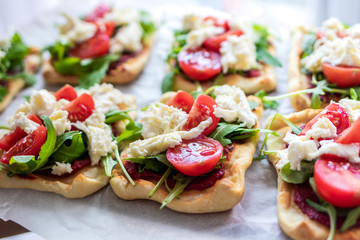 Mini pizza bites as appetizers, puff pastry as a base, topped with tomato puree, mozzarella and fresh ruccola.