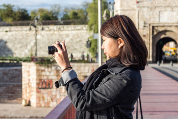 Chinese Girl Standing on the Bridge and Taking Picture With Her Photo Camera