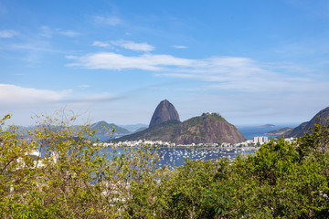 Sugarloaf mountain in Rio de Janeiro on a bright sunny day with blue sky with in the foreground Guanabara bay and the pleasure boat port of Botafogo